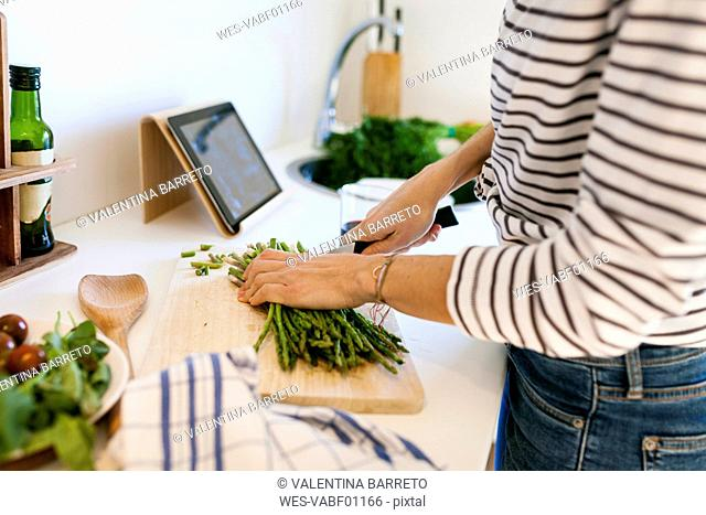 Young woman cooking at home using digital tablet for recipe
