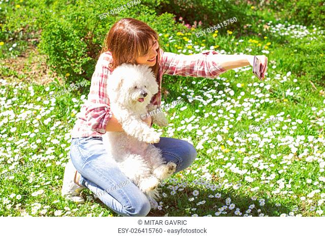 Happy beautiful young woman, enjoying nature with her dog, at sunny spring day in the park