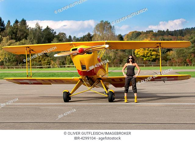 Young woman with sunglasses in overall and boots posing in front of double-decker airplane, fashion, lifestyle, photo shoot