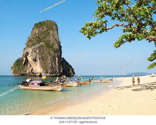 Thailand - Long-tail boats at the sandy Phranang Beach and limestone cliffs in the Andaman Sea  Phranang Peninsula, Krabi province, Southern Thailand