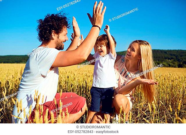 A happy family is enjoying fun with a child outdoors in a summer field