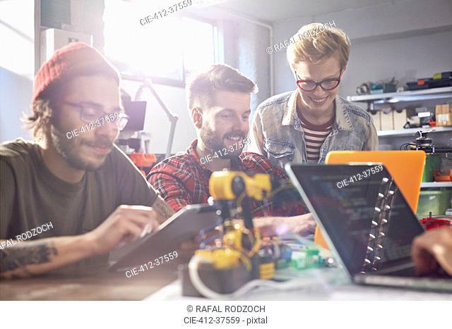 Computer programmers using laptops and digital tablet, programming robotics in workshop
