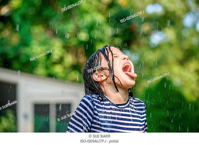 Young girl in garden, catching falling water in mouth