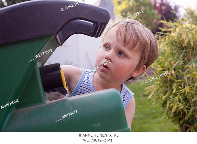Three year old boy looking at gardening machine trying to understand how it works. Sauerland,Germany