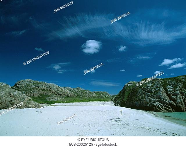 White Sand Beach with large moss covered bolders and a woman standing in the distance