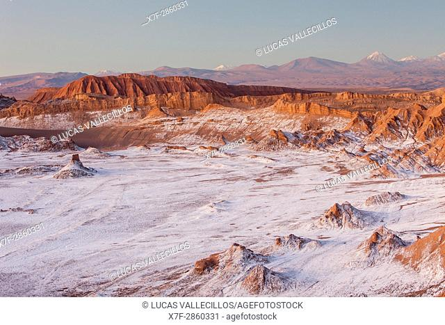 Valle de la Luna (Valley of the Moon ), in background Andes Mountains with snow on top , and salt deposited on the nearest mountains and ground, Atacama desert