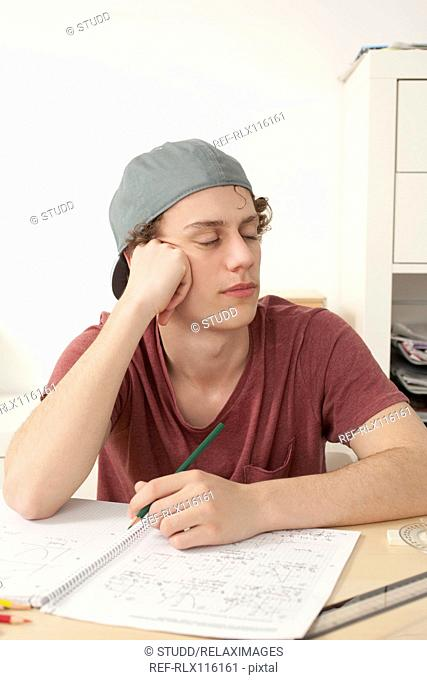 Stressed tired teenager doing homework