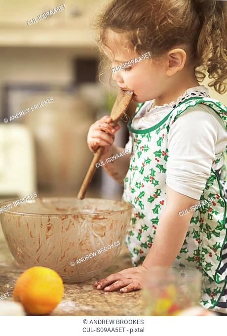 Child tasting cake mix with wooden spoon