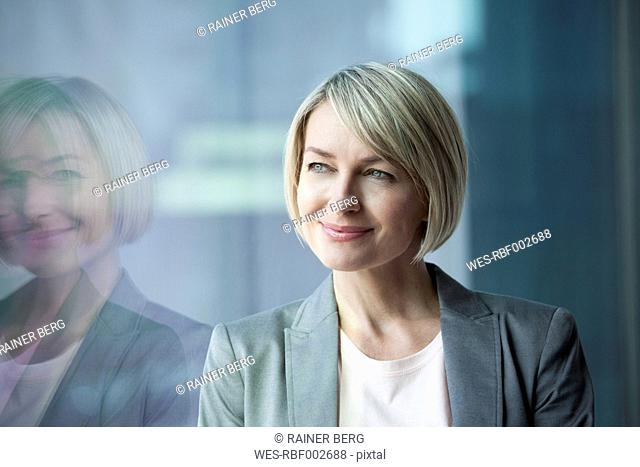Businesswoman standing at window, smiling, portrait