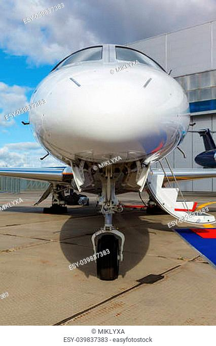 White reactive private jet, the front landing gear and a ladder