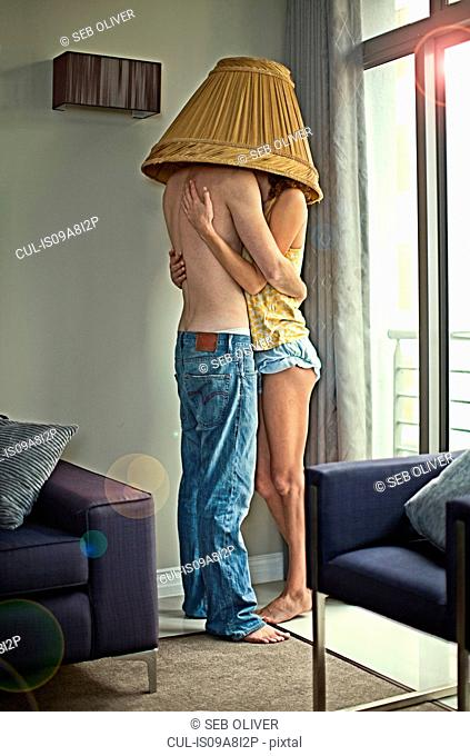 Young couple hugging under lampshade