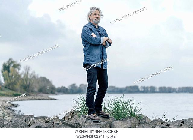 Senior man standing on stones looking at Rhine river