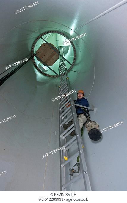 Alaska native wind turbine technican climbing a ladder inside the turbine, wearing a tool bag and harness, St. Paul Island, Southwestern Alaska, USA, Summer