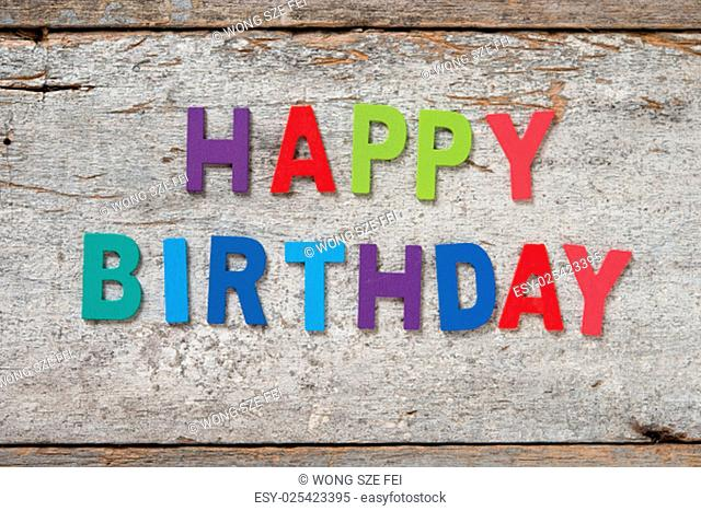 """The colorful words """"""""HAPPY BIRTHDAY"""""""" made with wooden letters on old wooden board"""