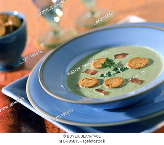 Creamed courgette soup with bread chips and bacon