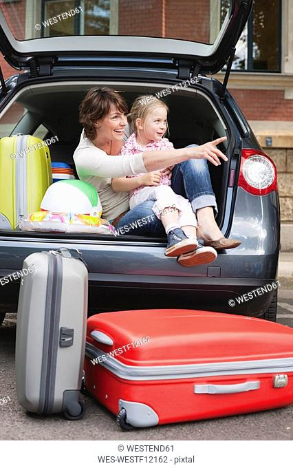 Germany, Leipzig, Mother and daughter 4-5 sitting in back of car, smiling, portrait