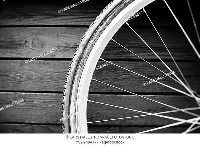 Transportation still life. Close up of bicycle wheel in front of wooden wall, Sweden