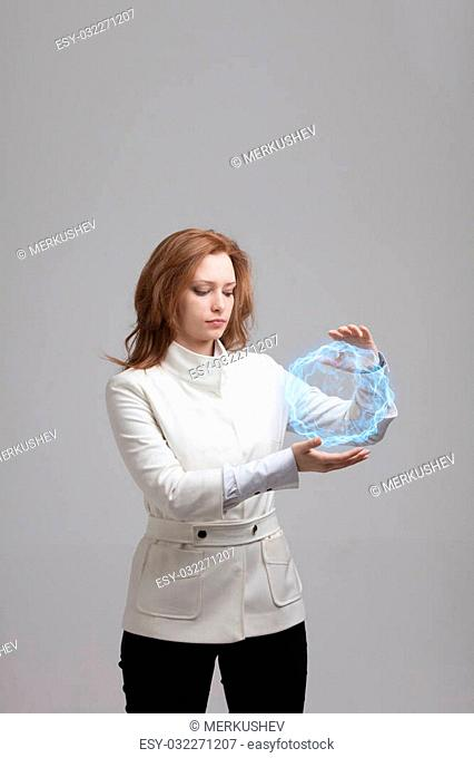 Woman with glowing magical energy ball on gray background