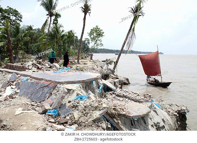 DHAKA, BANGLADESH - AUGUST 13 : Bangladeshi people take away their materials from homes being swallowed by the fury Padma River at Dohar Upazilla in Dhaka