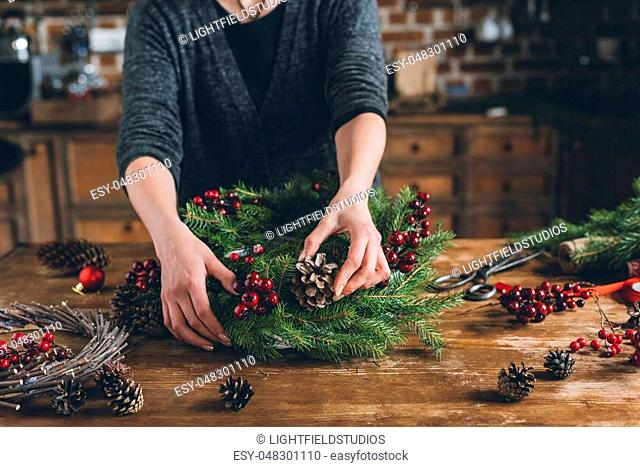 cropped view of florist making Christmas wreath of fir branches, decorative berries and pine cones at workplace