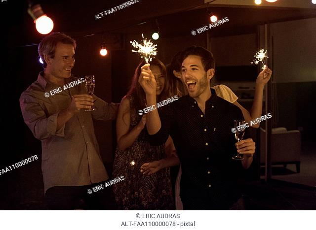 Friends celebrating with champagne and sparklers
