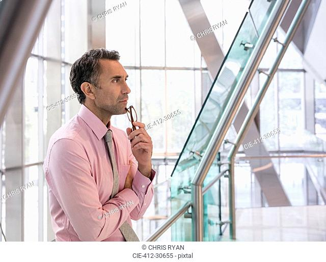 Pensive corporate businessman in modern office lobby