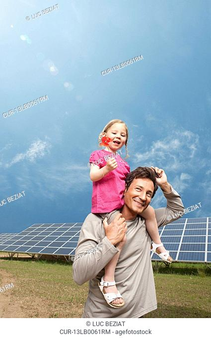 Man and daughter in front of solar panel