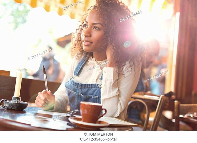 Pensive young woman writing postcard at cafe table