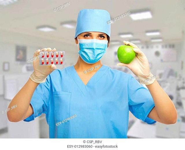 Doctor with apple and pill