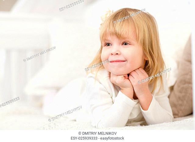 Happy pretty little girl lies on a sofa in the room