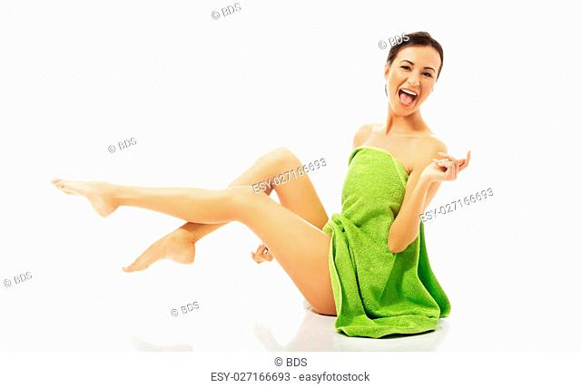 Laughing woman wrapped in towel with legs up