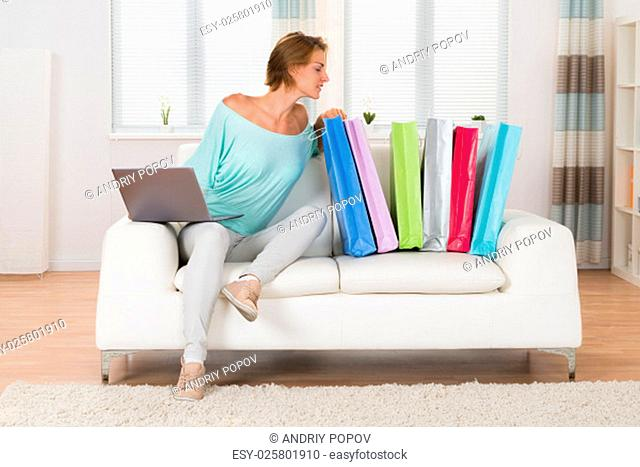 Young Woman On Sofa With Laptop Looking At Colorful Shopping Bags