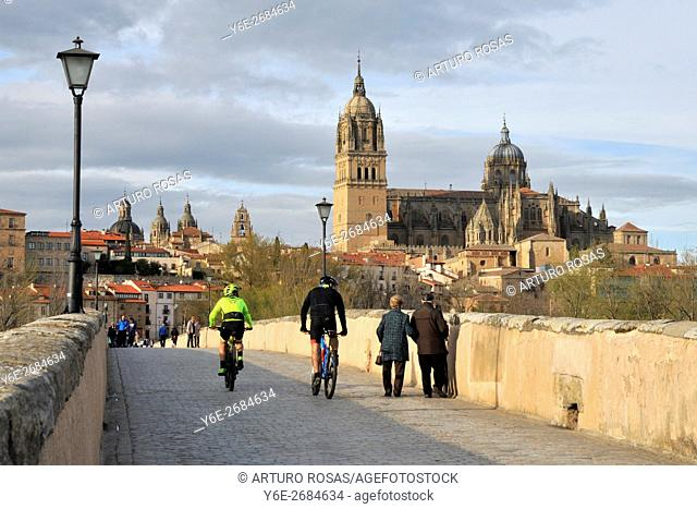 Two bikers and an elderly couple of pedestrian crossing the river Tormes over the Roman Bridge in Salamanca, Spain
