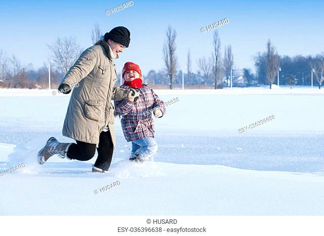Mom and daughter running in the snow