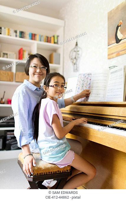 Portrait smiling mother and daughter playing piano