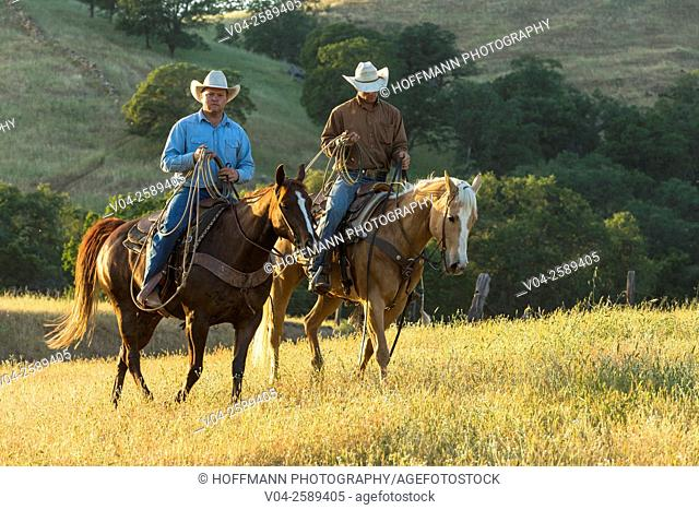 Two wranglers (cowboys) on horses, California, USA