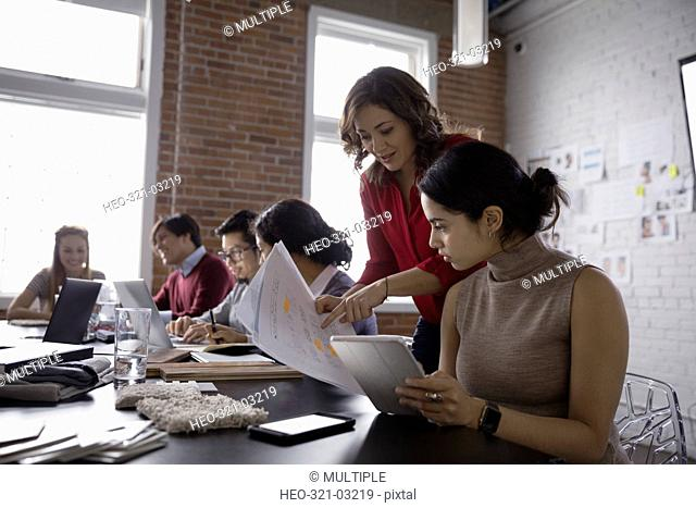 Female hispanic designers reviewing paperwork in conference room meeting