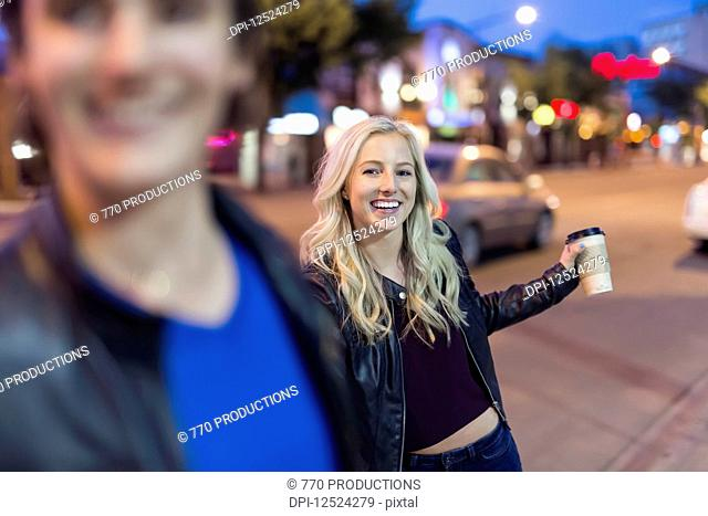 A young couple being playful on the sidewalk beside a city street at dusk; Edmonton, Alberta, Canada