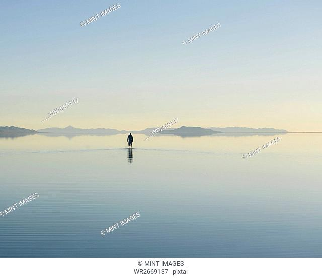 Man walking on vast and flooded Bonneville Salt Flats, Utah