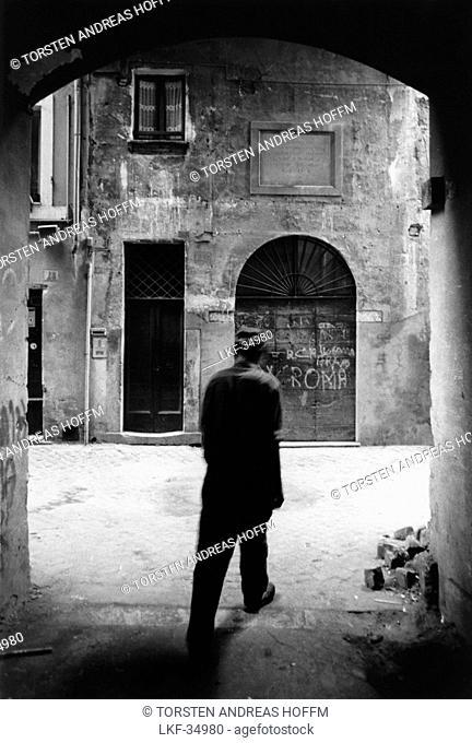 Man walking through a gate on the street, Rome, Italy
