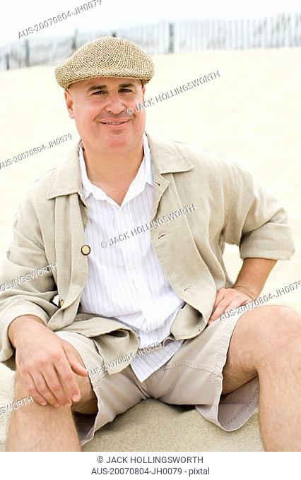Portrait of a mature man sitting on the beach and smiling
