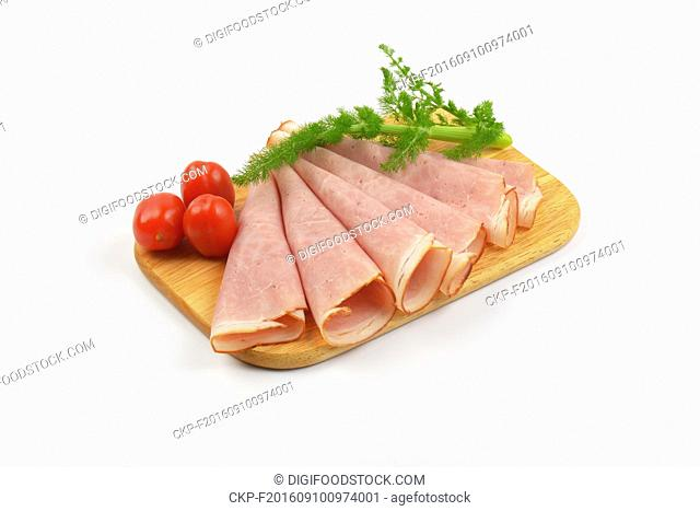 ham slices with dill an cherry tomatoes on wooden cutting board