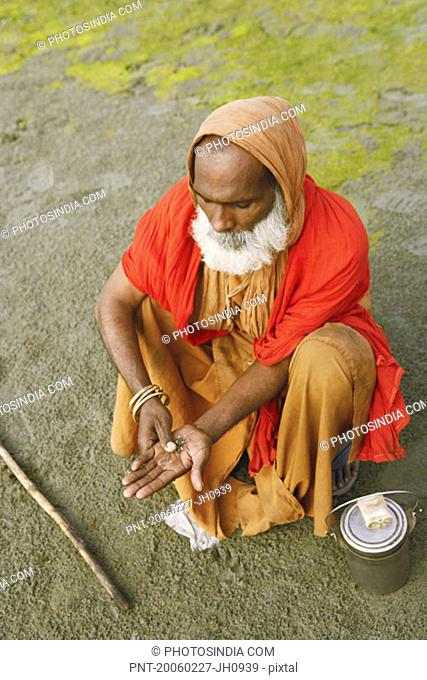 High angle view of a priest rubbing tobacco in his palm, Agra, Uttar Pradesh, India