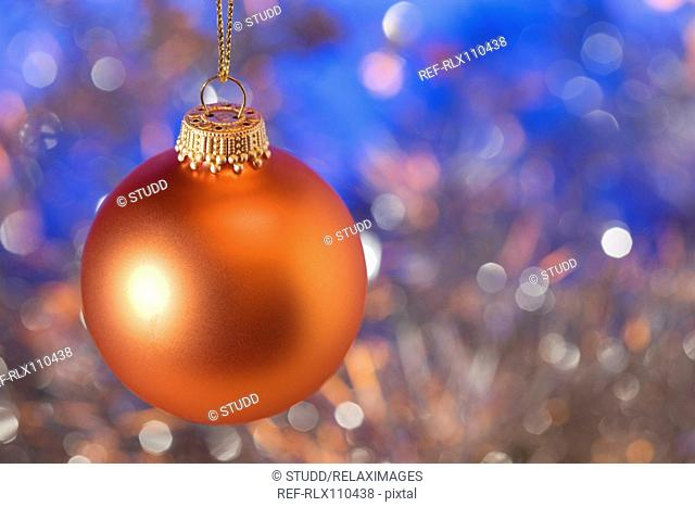 Orange Christmas bauble with blue background, close-up