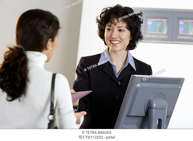 Airline employee assisting a customer at ticket counter