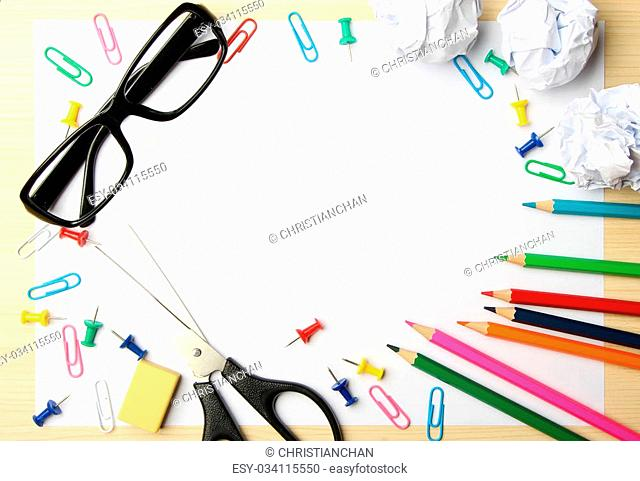 School supplies with white paper on the wood desk background