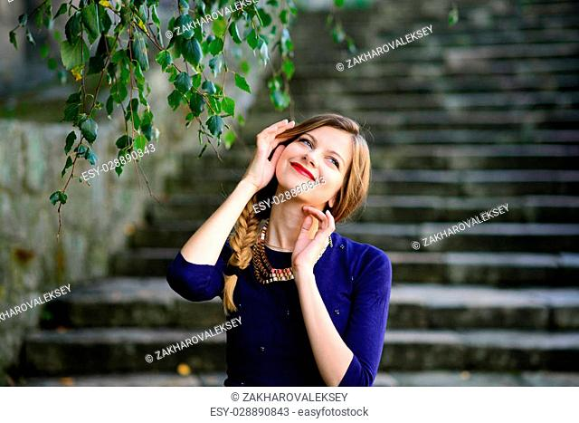 high girl posing in blue dress standing on stone stairs