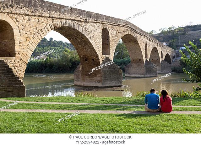 Couple sitting near the Medieval bridge in Puente La Reina - Navarre, Spain. Queen Doña Mayor, wife of King Sancho III, built the six-arched bridge over the Río...