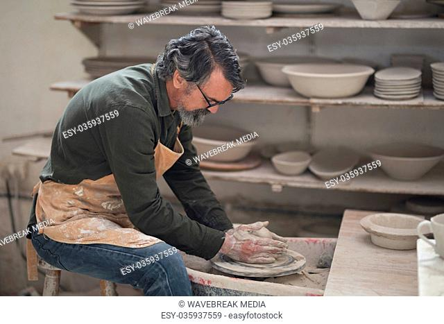 Male potter molding a clay