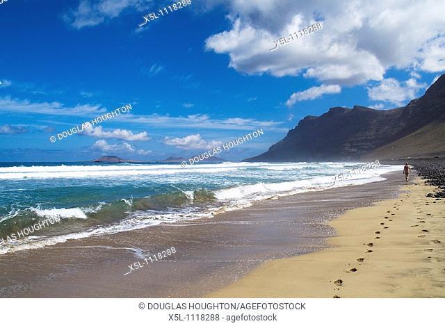 Playa de Famara FAMARA LANZAROTE Tourist man walking along sandy beach El Risco de Famara sea cliffs and bay